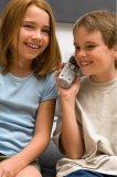 Portrait of two young kids talking on the same telephone.